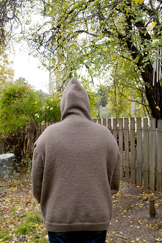 Photo of Ruth wearing the knitted jumper. Taken from behind with the hood up