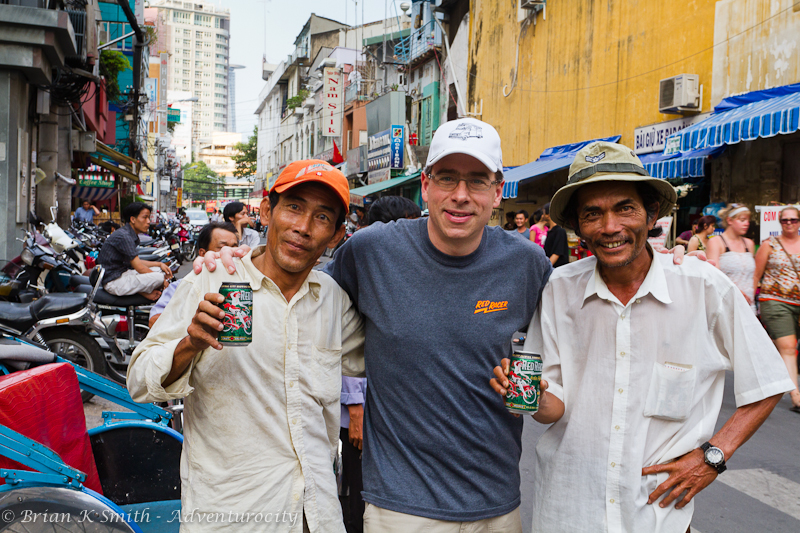 Rick Green sharing Red Racer IPA with two Saigon cyclo drivers.