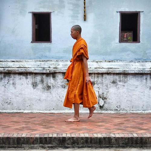 Monk walking past Wat Sensoukaram.  Luang Prabang, Laos. by daveweekes68