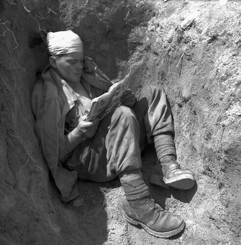 Private G.U.I. Lambert, 2nd Battalion, Royal 22e Regiment, reads a comic book in a slit trench, Korea / Le soldat G.U.I. Lambert, 2e Bataillon du Royal 22nd Régiment, lit une bande dessinée dans une tranchée en Corée