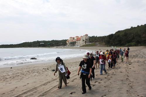 一群人從杉原灣出發,踩著沙灘,美麗灣飯店目送群人離開