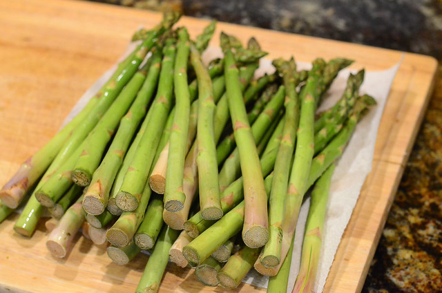 Asparagus stacked on top of a cutting board.
