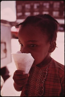 Black Ghetto Child Savors A Snow Cone Just Received From A Sidewalk Vendor On Chicago's West Side, 06/1973