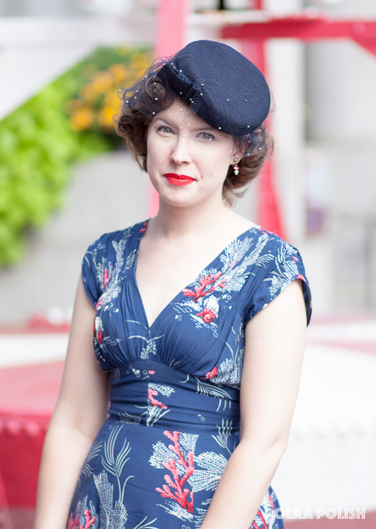 A vintage navy blue tilt hat with a dotted veil pairs perfectly with this ocean-themed novelty print dress from Trashy Diva