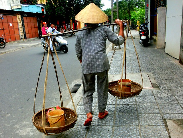 A woman in a conical hat walks down a street in Hoi An