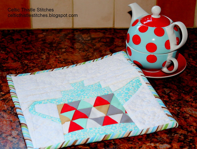 Paper-pieced teapot block quilted and bound as a teapot stand