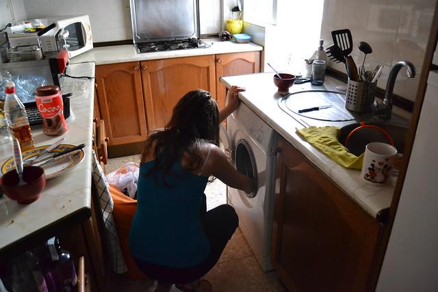 Estudiante achicando agua de una lavadora estropeada
