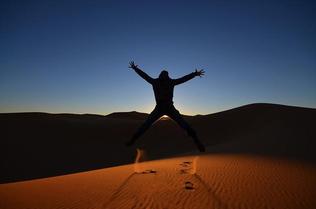 Saltando al amanecer en el desierto de Marruecos en una excursión desde Marrakech que hicimos a Erg Chebbi