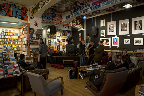 People sat around in a record shop chatting
