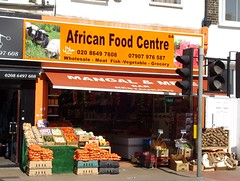 "A photo taken on a bright, sunny day of a small terraced shopfront with neatly-displayed vegetables outside on the pavement.  A sign above reads ""African Food Centre / 020 8649 7608 / 07907 976 587 / Wholesale - Meat Fish - Vegetable [sic] - Grocery"" in black letters on an orange background.  A photo of sheep in a field is on the left of this sign, a photo of some sort of red cubed food is on the right, and the word ""Halal"" in English and Arabic is printed in white.  A canopy reads ""Mangal & Meze Bar Restaurant"".  The shopfront is completely open, though the lighting of the photo makes it hard to see much inside."