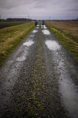 Cycling along a gravel road on the Ishikari River floodbank (Ebetsu, Japan)