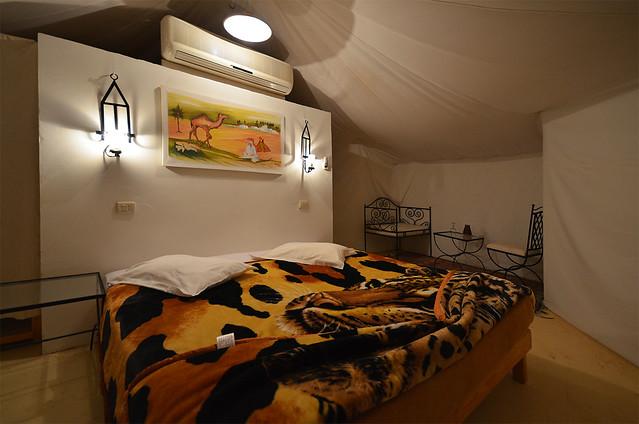 Interior de mi jaima en el desierto de douz con una colcha con un tigre y cabecero con un cuadro del desierto con camellos