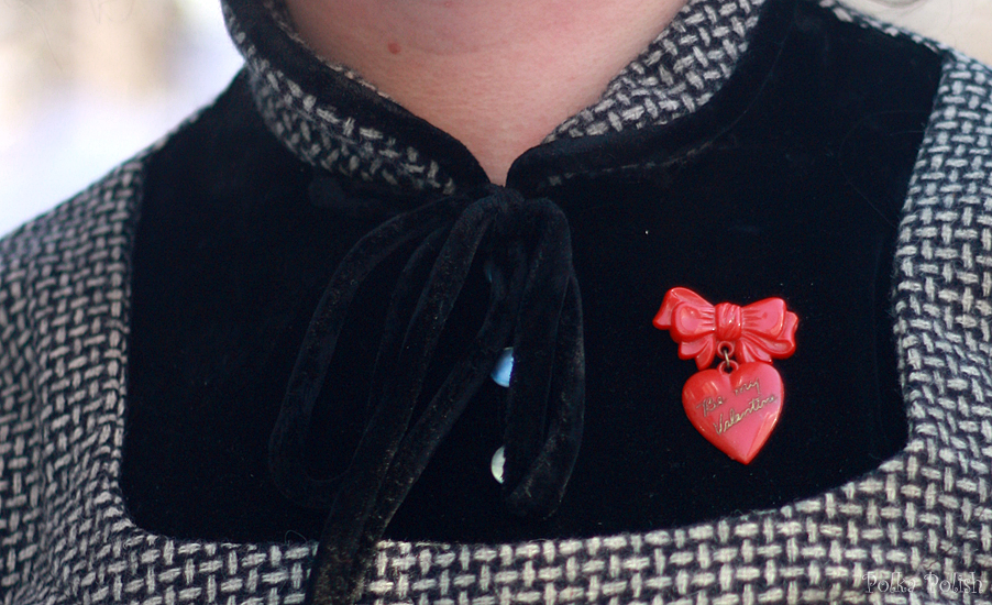 "Detail of a ""Be My Valentine"" red heart-shaped novelty brooch paired with a vintage wool dress with black velvet details"
