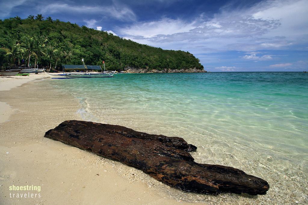 dead log adrift at Puting Buhangin Beach and Kwebang Lampas
