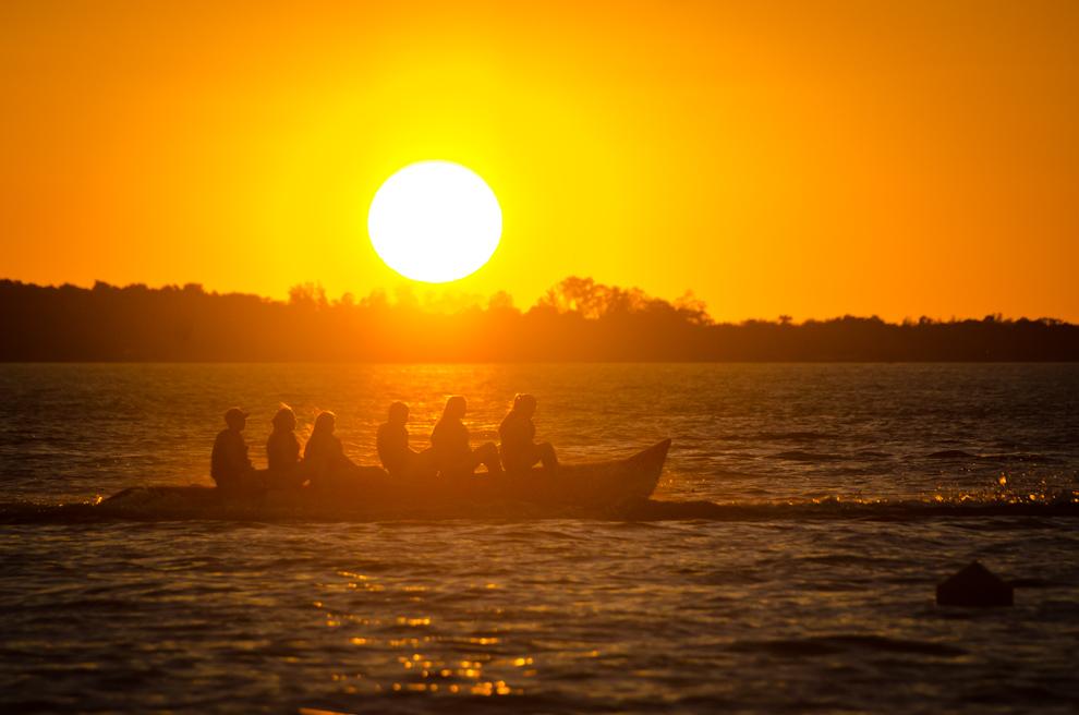"""Jóvenes se divierten en la """"banana"""" mientras el sol va cayendo en el horizonte sobre el Río Paraná en la playa San José de la ciudad de Encarnación. (Elton Núñez)"""