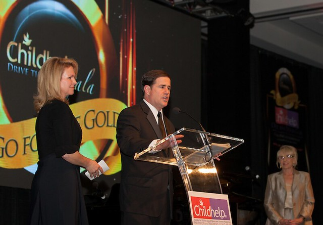 Angela and Gov. Doug Ducey address attendees of the Drive the Dream Gala while the Honorable Jan Brewer looks on