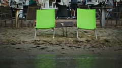 Two empty chaise-lounges with table on the beach