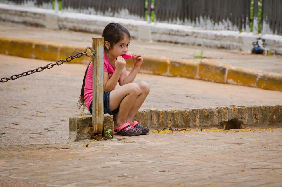 Una niña aplaca el calor con un helado de frutilla mientras sus padres toman fotografías en una plaza del centro de la ciudad de San Pedro, en el Departamento de San Pedro. (Elton Núñez)