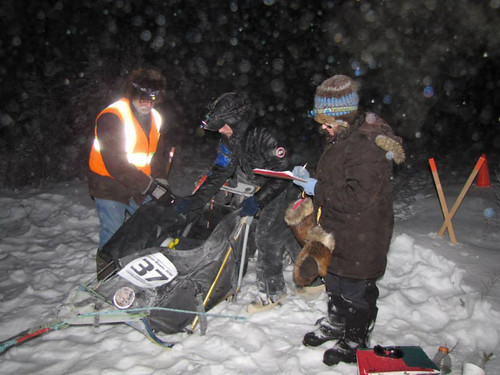 Bureau of Land Management volunteers Marnie Graham and Dennis Teitzel check in a racer at the Sourdough checkpoint for the Copper Basin 300 dog sled race in Alaska. (National Park Service)