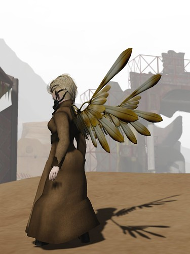 Image Description: Figure in a tan duster with gold wings looking down into a town.