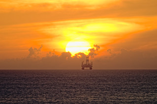 Oil rig touching the yellow sun and orange sunset clouds off the Bahamas in the Atlantic Ocean's shipping lanes