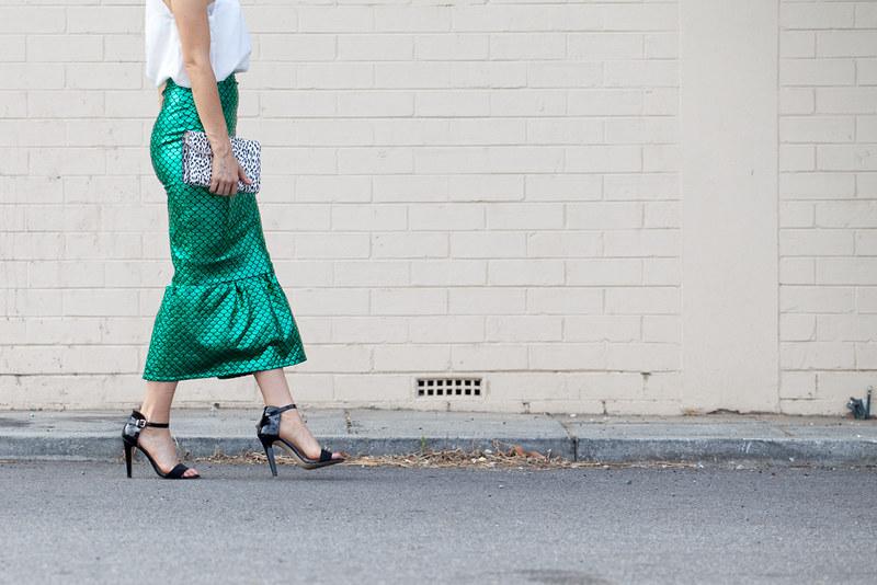 Walking shot of green metallic skirt and black heels
