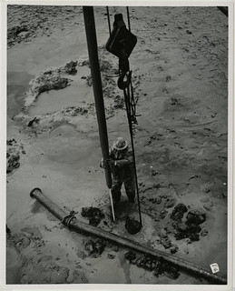 2/65. Cordova - Workman guides a jet of water that is used to free embedded piling in the way of the dredge, originally placed as a support to old city dock