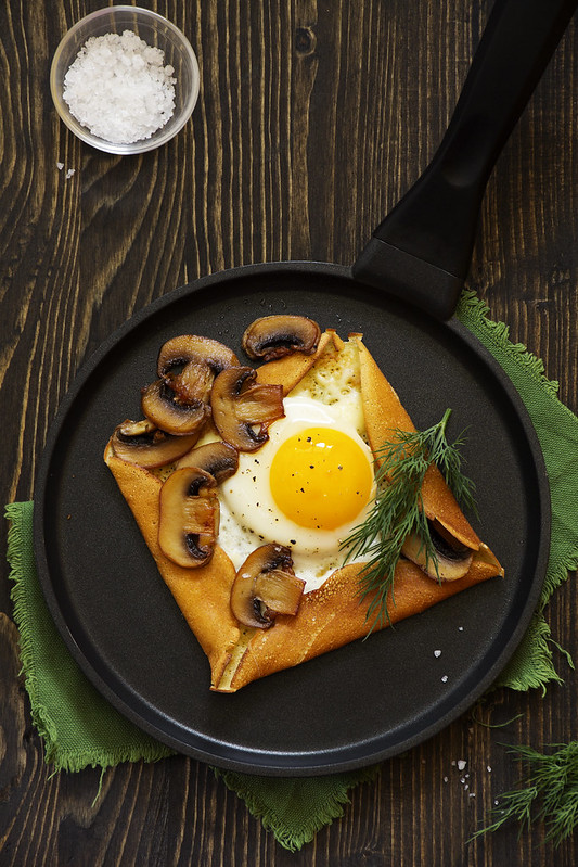 Pancakes with fried egg and fried mushrooms.