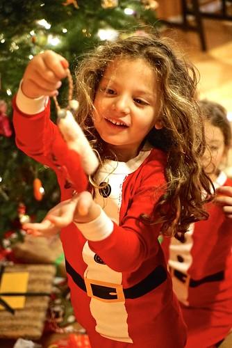 Hazel hangs an ornament on the tree