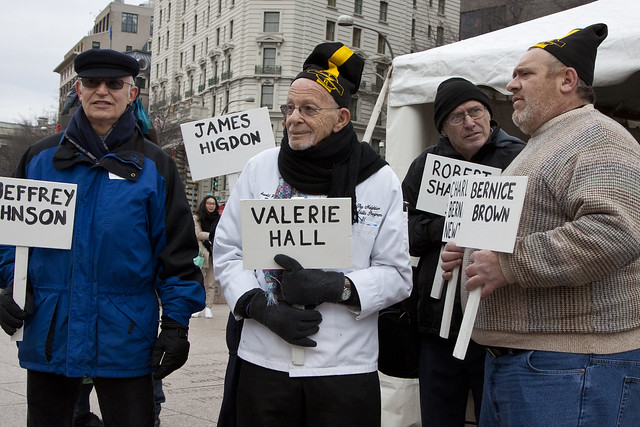 Arnold Abbott (second from left) and Michael Stoops (second from right) hold signs in the cold, remembering those who have died homeless in 2014.  Photo by Jane Cave