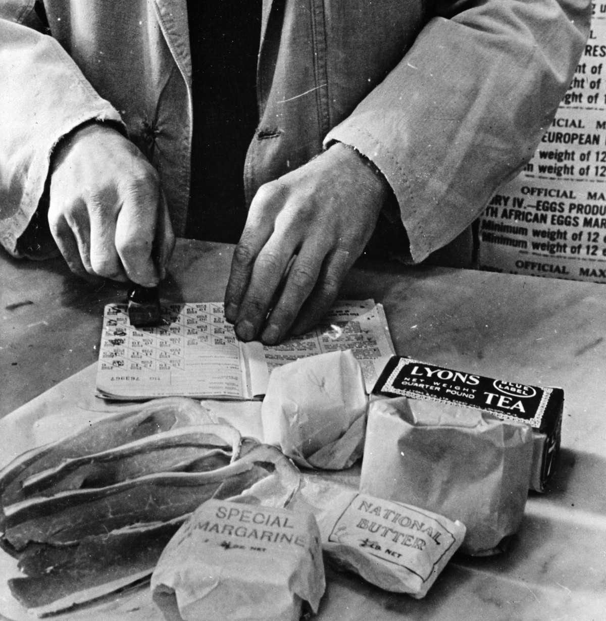 "A shopkeeper cancels the coupons in a British housewife's ration book for the tea, sugar, cooking fats and bacon she is allowed for one week. Most foods in Britain were rationed and some brand names are given the designation ""National""."
