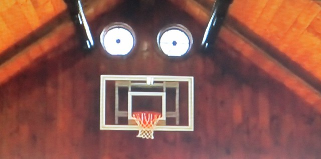 Photo of TV screen showing an indoor basketball court (face) in a very high-end home