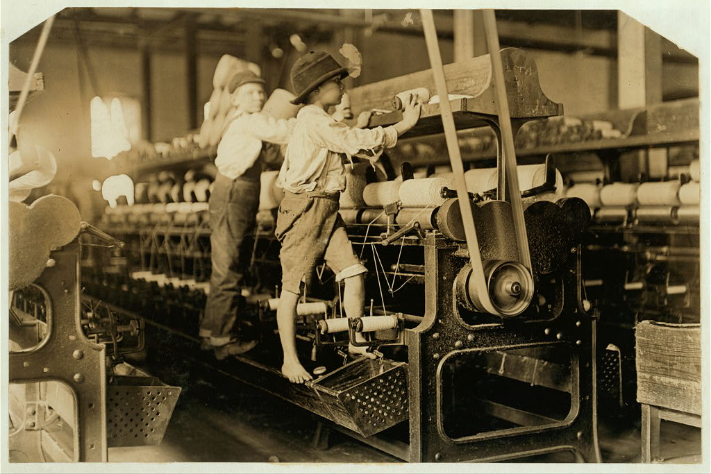 488 Macon, Ga. Lewis W. Hine 1-19-1909. Bibb Mill No. 1 Many youngsters here. Some boys were so small they had to climb up on the spinning frame to mend the broken threads and put back the empty bobbins. Location: Macon, Georgia.