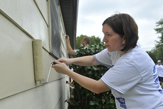 Chief Petty Officer Allyson Vaskey, a storekeeper at Shore Infrastructure Logistics Center in Norfolk, Va., puts a fresh coat of paint on a home in Hampton, Va., Saturday, Oct. 11, 2014. Vaskey was part of a group of Coast Guard volunteers with the Habitat for Humanity program. (U.S. Coast Guard photograph by Petty Officer 3rd Class Nate Littlejohn)