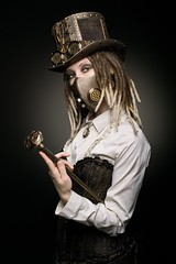 steampunk girl in top hat goggles gaz mask corset with belt and walking stick