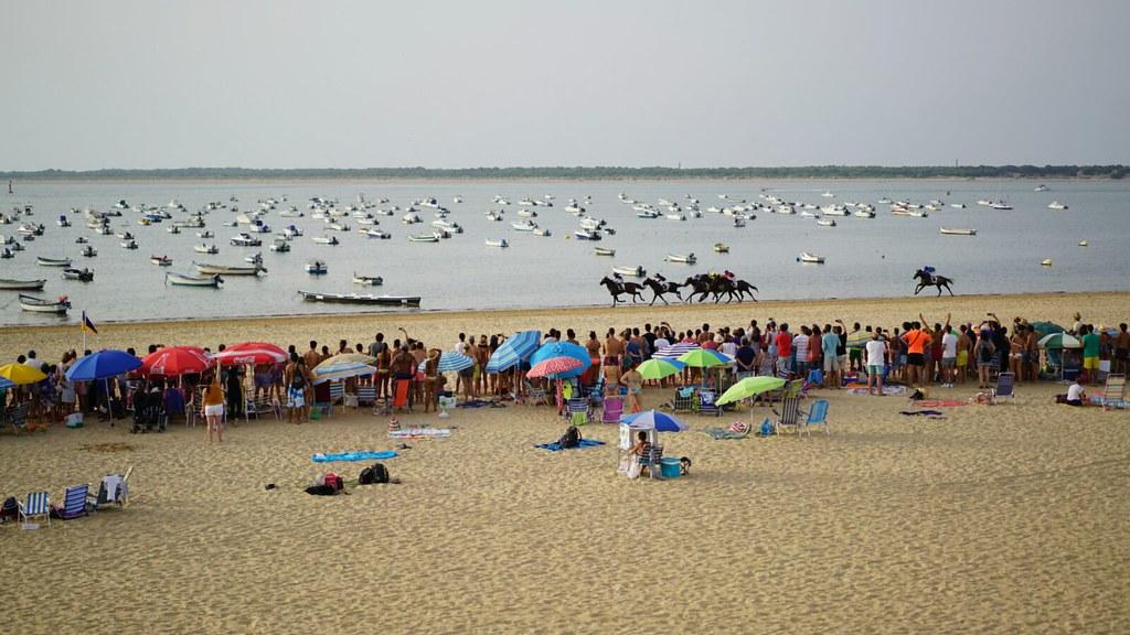 Vista general de la carrera de caballos de Sanlúcar con el público en la playa y los barcos en el fondo