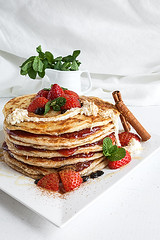 White plate full of pancakes with raspberries stra…