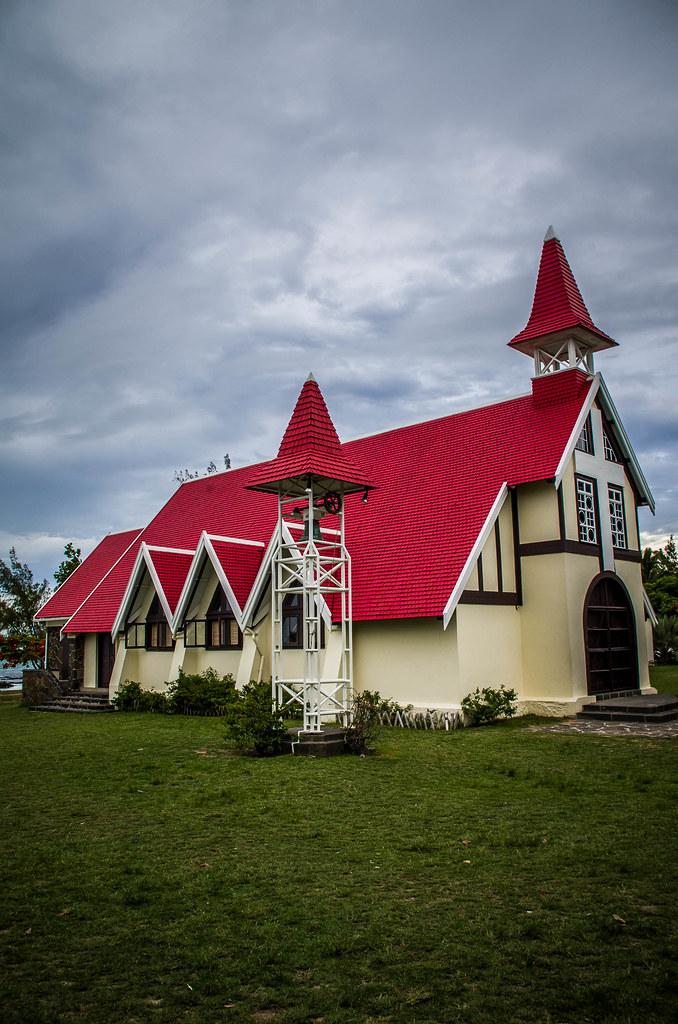 Eglise : Toit du Clocher de Tuile Rouge Cloche et Herbe et Parvis Vert de Jour sous Nuage Gris et Sombre