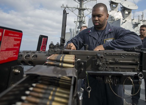 U.S. 5th Fleet Area of Operations - Ship's Serviceman 1st Class Derome D. Smith learns to gauge an M2HB .50-caliber machine gun aboard the guided-missile destroyer USS Dewey (DDG 105) during a training exercise.