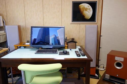 My Room_(2015_02_10)_1 部屋の写真。中央にはPC ディスプレイとキーボードとマウスとオーディオ装置用リモコンが置かれたテーブルと黄緑色の回転椅子があり、奥にはフロント チャネル用の大きなトール ボーイ型スピーカー システムが2本あり、右端には大きなサブウーファーが置かれている。PC ディスプレイにはUbuntu OSのデスクトップが表示されている。壁に掛けられた額には黄色い月の写真が収められている。