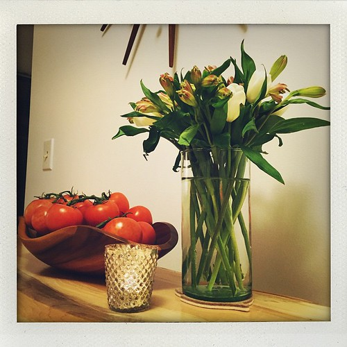 White tulips, alstroemeria, mercury glass votive, & tomatoes on the vine
