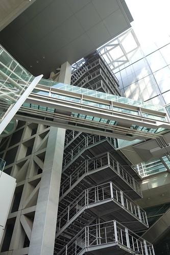 """Tokyo_23 東京都丸の内の """"東京国際フォーラム"""" の写真。 鉄骨の螺旋外階段とガラス張りの空中通路とその床下の3本の金属の配管とコンクリート造りの格子状の巨大な柱が画像に写っている。"""