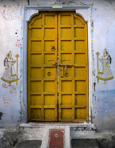 A yellow door in a painted wall in Udaipur, India