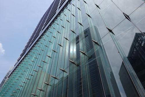 "Shimbashi_10 新橋で撮影した高層ビルディングの写真。 ""汐留住友ビル""。 直下から見上げる角度で撮影。 下層部分は緑色掛かったガラス張り。 ガラス張りの下層部分の上から下まで連なった垂直なガラス板が左端から右端まで等間隔に突き出ている。"