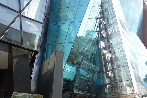 "Shibuya_24 渋谷の明治通りに面した所にある高層ビルディングを撮影した写真。 右の ""THE ICEBERG ビルディング"" の前面はターコイズブルー色のガラス張りで複雑な三次元ジオメトリック構造をしている。 左の ""J6Frontビル"" は前面が数多の三角形のガラス張りである。"
