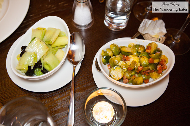 Side dishes of buttered leeks and prunes and sautéed brussels sprouts with chorizo