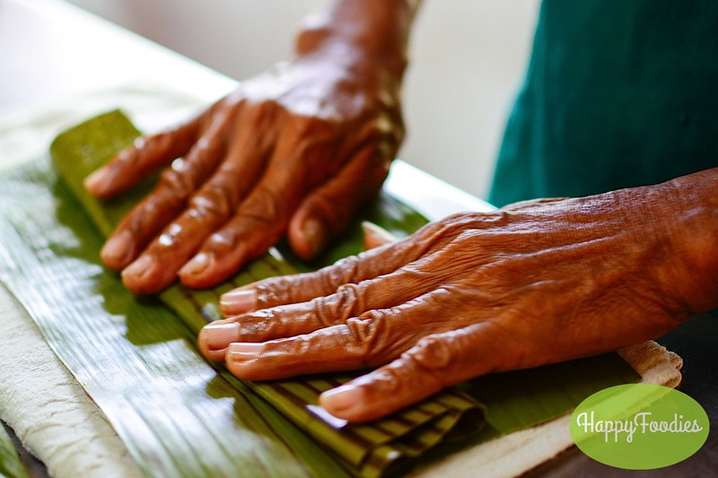 Carefully wrapping the suman with banana leaves