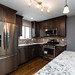 Custom gray tone cabinetry, hardwood floors, Alaskan white granite, recessed and pendant lighting tile backsplash and stainless appliances