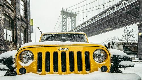 Yellow Jeep covered in snow near manhattan bridge view area in Brooklyn.