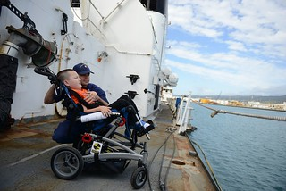ix-year-old Jacob Butierries enjoys the view of Honolulu Harbor from the Coast Guard Cutter Rush with his father Petty Officer 1st Class Denis Butierries during a tour of the ship Dec. 23, 2014. Jacob was diagnosed with spinal muscular atrophy when he was four months old and was given four months to one year to live. His longtime wish was to see the Rush where his grandfather served as the engineering officer.
